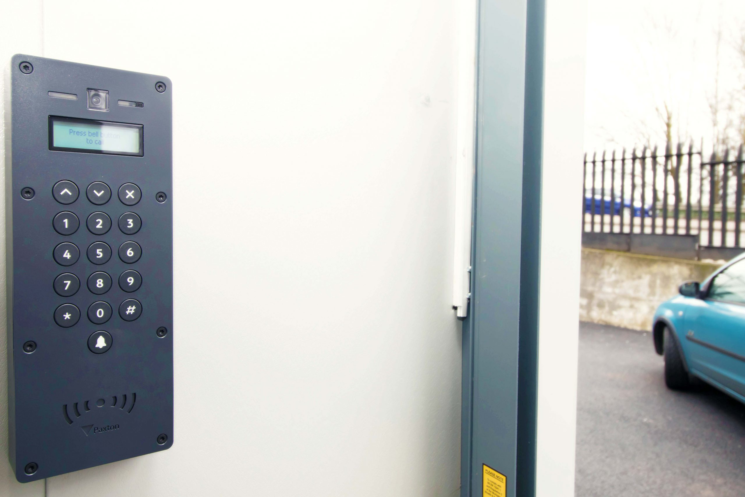 An access contril system on an external door, leading our onto a road.